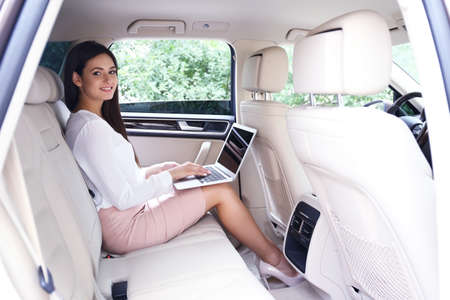 Young businesswoman with laptop on back seat in car