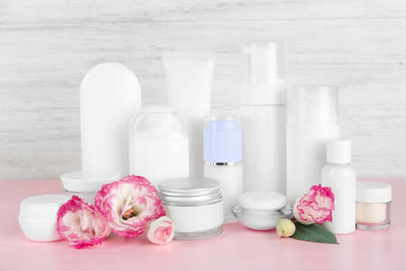 Different cosmetic bottles and flowers on grey wall background