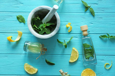 Bottles with mint oil and mortar with fresh leaves on wooden background, top view Stock Photo