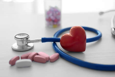 Red heart with stethoscope and pills on table Stock Photo