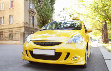 Yellow taxi car on city road Stock Photo