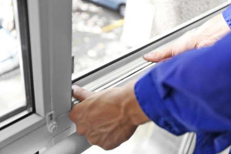 Bauarbeiter, der Dichtungsschaumband auf Fenster in Haus einsetzt Standard-Bild