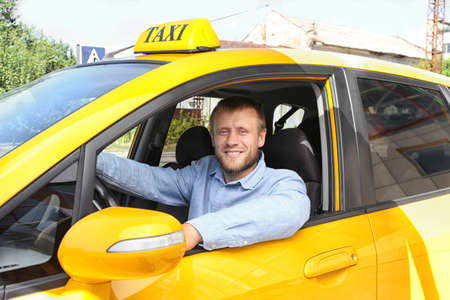 Handsome taxi driver sitting in car Stock Photo