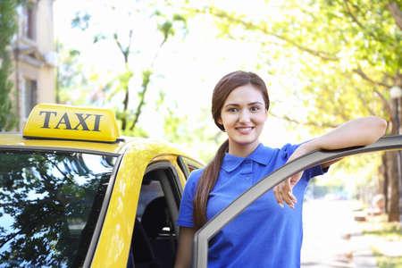 Beautiful female taxi driver standing near car Foto de archivo