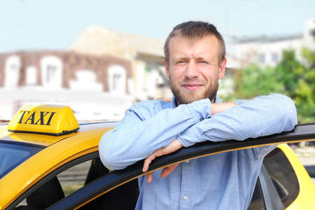Handsome taxi driver near car on station