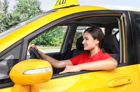 Beautiful female taxi driver sitting in car Stockfoto