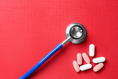 Stethoscope with pills on table Stock Photo