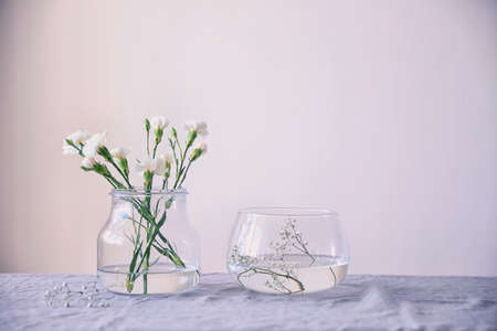 Glass vases with flowers on table Stock Photo