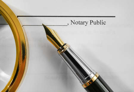 Notary public document, magnifier and fountain pen, close up view Imagens