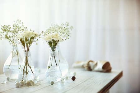 Mini glass vases with flowers on table
