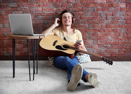 Young man playing guitar and composing song in room Stock Photo - 96714555