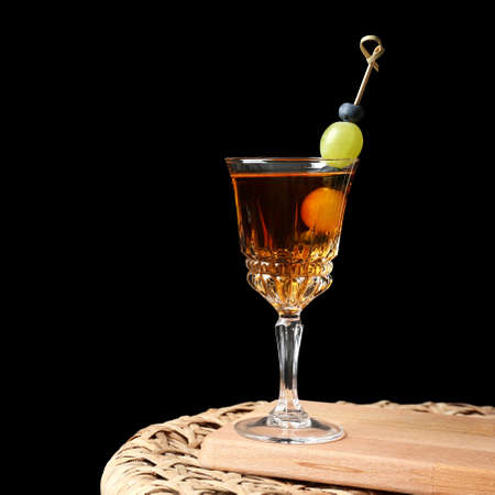 Tasty cocktail on wicker table and black background
