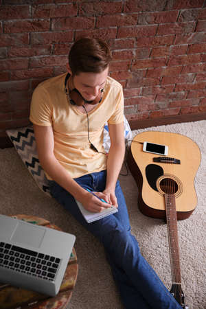 Young man composing a song and sitting on the floor against a brick wall