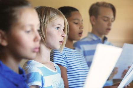 Dzieci w wieku szkolnym śpiewają piosenkę na lekcji muzyki
