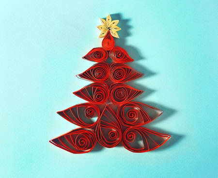 Christmas tree made of paper on color background