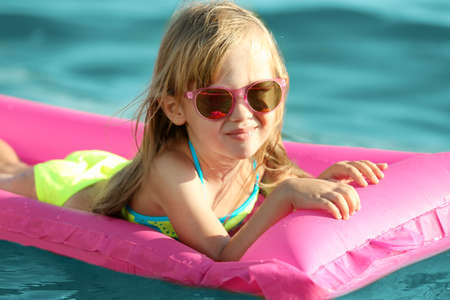 Cute girl swimming on inflatable mattress