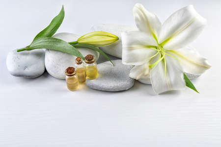 Spa stones, beautiful lily and bottles with aroma oil on white wooden background