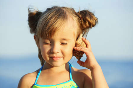 Cute girl listening to seashell at sea