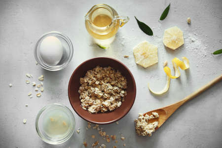 Natural scrub made of oatmeal, olive oil and lemon on light background