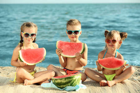 Cute kids eating watermelon on beach