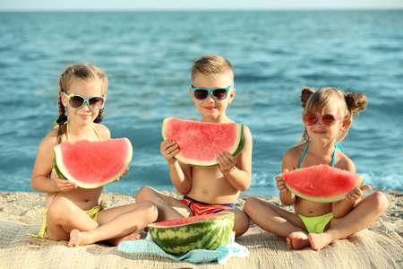Cute kids eating watermelon on beach