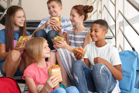 Schoolchildren eating sandwiches while sitting on stair-steps at school