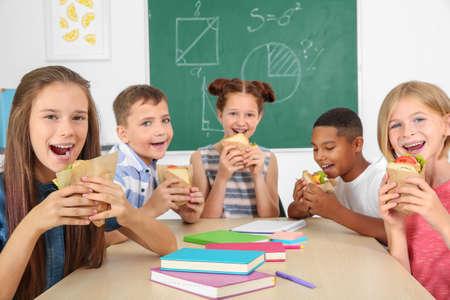 Schoolchildren having lunch in classroom Stock Photo