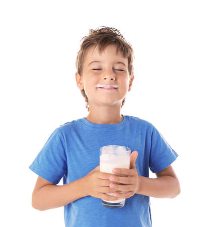 Cute boy in blue shirt holding glass of milk on white background