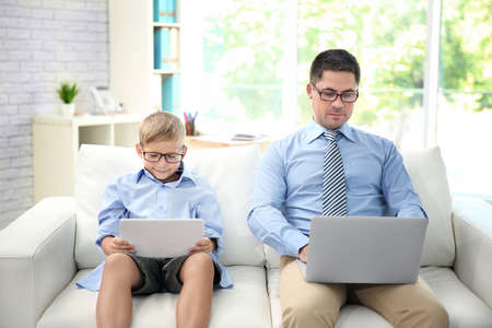 Little son with tablet and father with laptop sitting on sofa at home