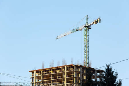 Construction crane and building on blue sky background