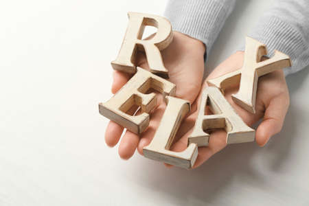 Word Relax Of Wooden Letters In Female Hands And On White Background