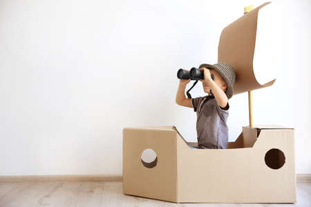 Little boy playing with cardboard ship on white wall background Stockfoto