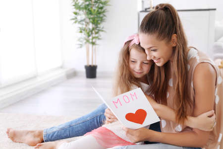 Cute girl and mom with handmade greeting card. Mothers day concept