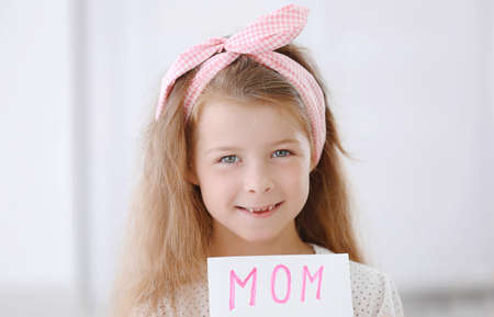 Cute girl with handmade greeting card for mother at home