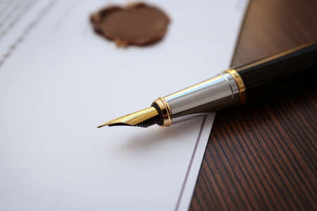 Fountain pen and old notarial wax seal on document, closeup Stock Photo