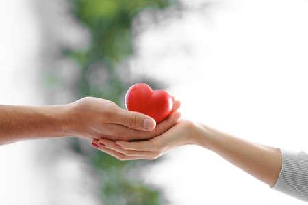 Manos de pareja con corazón rojo, primer plano Foto de archivo