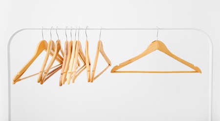 Wooden coat hangers on clothes rail and white background Reklamní fotografie - 96367134