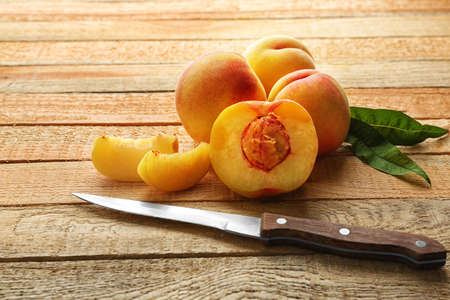 Fresh juicy peaches and knife on wooden background Фото со стока