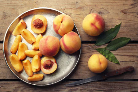 Fresh juicy peaches in silver tray and knife on wooden background
