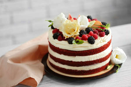 Delicious cake with fruit and berries decoration on white table