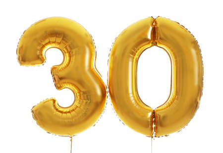 Golden birthday balloons on light background