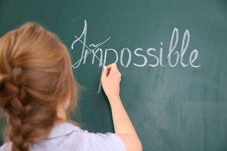 Woman transforming IMPOSSIBLE into POSSIBLE on chalkboard Archivio Fotografico
