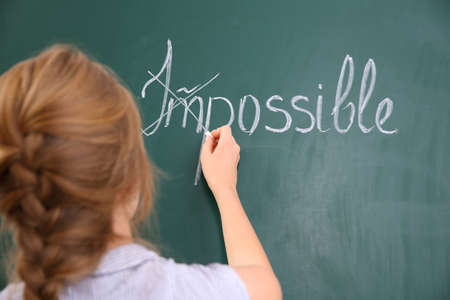 Woman transforming IMPOSSIBLE into POSSIBLE on chalkboard Stock Photo