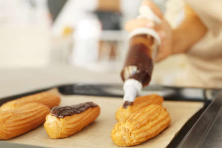 Decorating delicious homemade eclairs with chocolate on baking tray Banque d'images