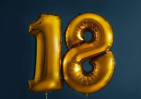Golden birthday balloons on dark background Stock Photo