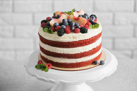 Delicious cake with fruit and berries decoration on gray table Foto de archivo