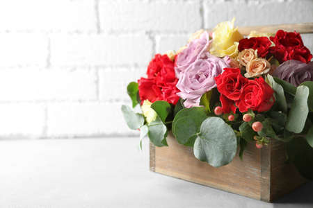 Beautiful flowers in wooden box on light background