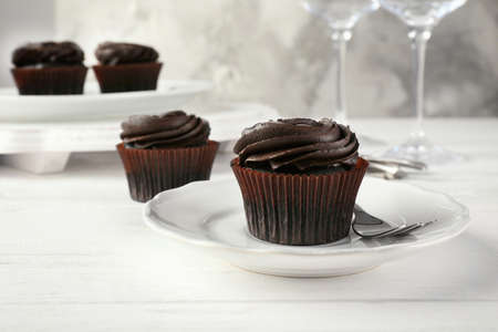 Tasty chocolate cupcake on plate