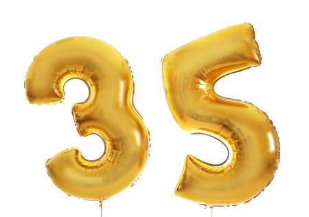 Golden birthday balloons on light background Stock Photo