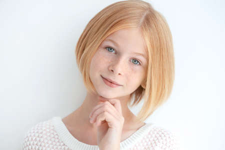 Portrait of attractive teenager girl with freckles on white background